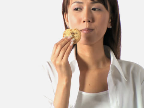 one young woman is eating a piece of cookie - スイーツ点の映像素材/bロール
