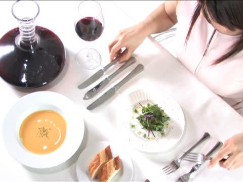 vidéos et rushes de one young woman is having a meal - seulement des jeunes femmes