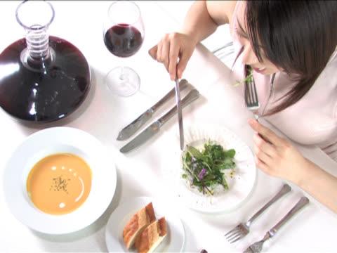 one young woman is having a meal - テーブルマナー点の映像素材/bロール