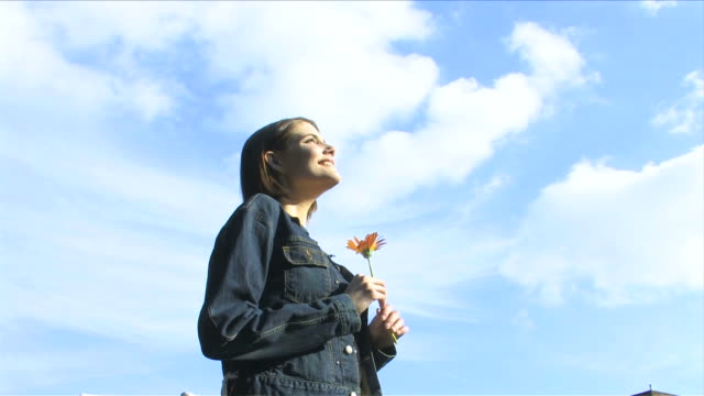One young woman is holding flower