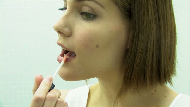 One young woman is making up using a lipstick