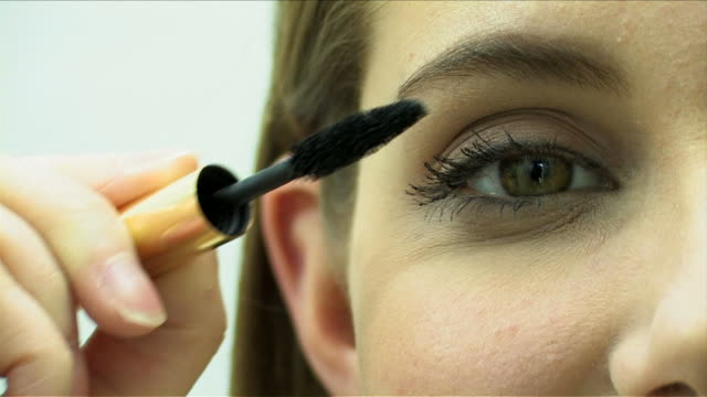 One young woman is making up using mascara