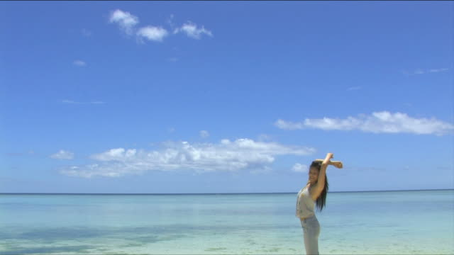 one young woman is stretching on the beach with smile   - 体を伸ばす点の映像素材/bロール