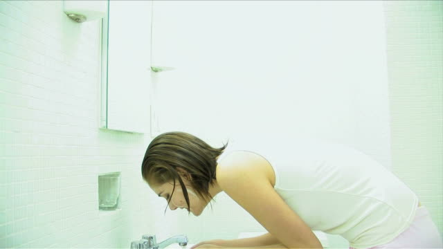One young woman is washing her face