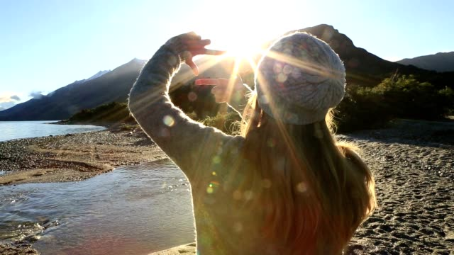 One young woman makes a hand finger frame  over sunset.