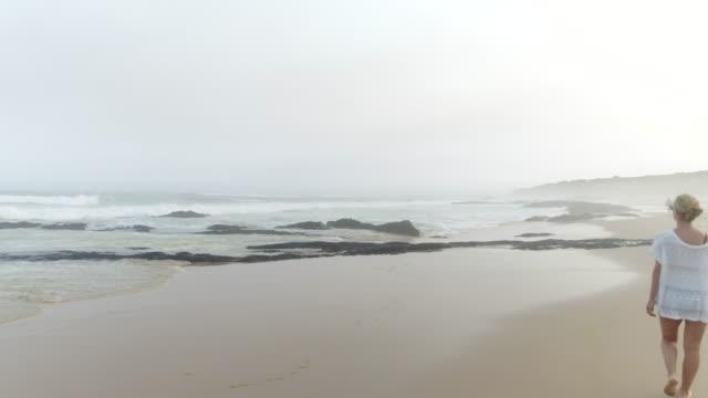 eine junge frau, die zu fuß am strand in südafrika, 4k - in den zwanzigern stock-videos und b-roll-filmmaterial