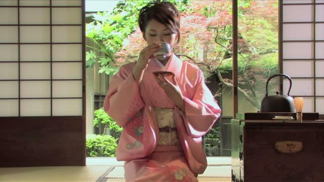 one young woman wearing kimono is drinking tea - kimono stock videos and b-roll footage