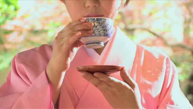 one young woman wearing kimono is drinking tea - 温かいお茶点の映像素材/bロール