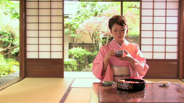One young woman wearing kimono is eating sushi