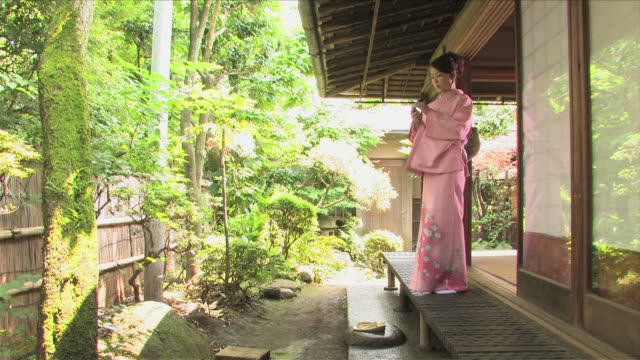 One young woman wearing kimono is in Japanese traditional house