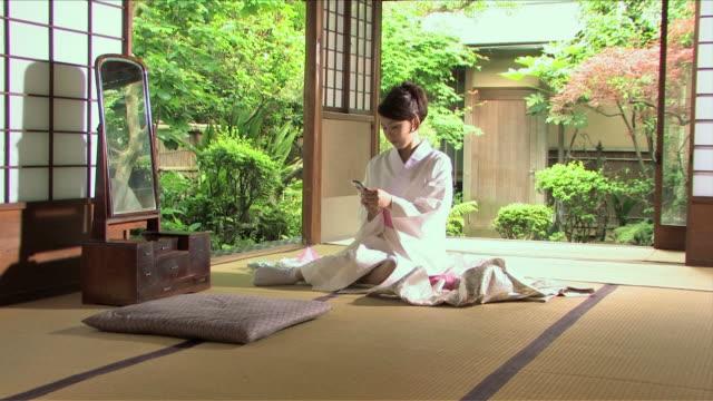 vídeos y material grabado en eventos de stock de one young woman wearing kimono is making a phone call - sólo mujeres jóvenes