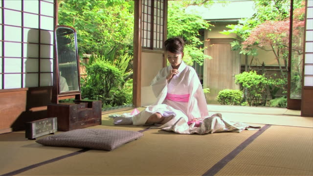 one young woman wearing kimono is sitting in japanese traditional house - kimono stock videos & royalty-free footage