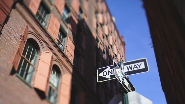 one-way road signs stand beside the many opened pink steel window doors at loft building along the alley in soho district at new york city ny usa on may. 22 2019. - vicolo video stock e b–roll