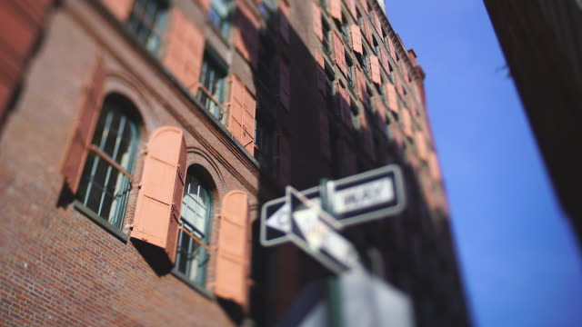 one-way road signs stand beside the many opened pink steel window doors at loft building along the alley in soho district at new york city ny usa on may. 22 2019. - loft apartment stock videos & royalty-free footage