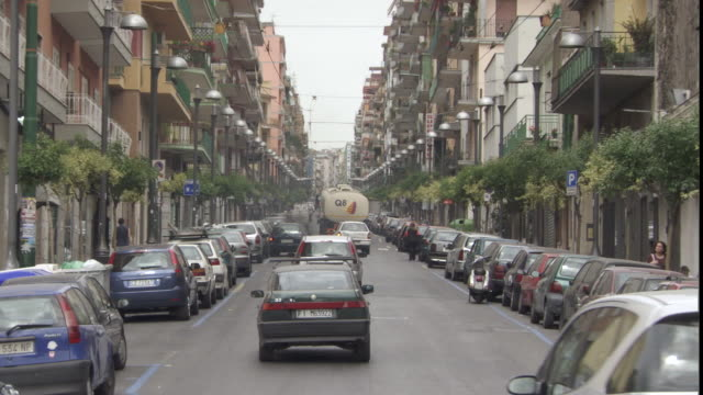 ws one-way street with traffic, buildings and parked cars / naples, campania, italy - ナポリ点の映像素材/bロール