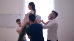 сonfidence and trust, girl falls on back and colleagues catch her and then applaud on group therapy