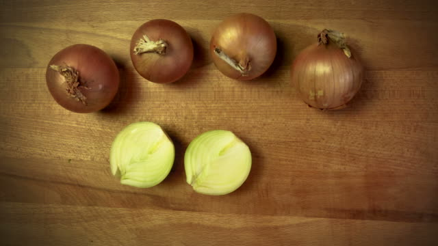 Onion. Moving vegetables on kitchen table