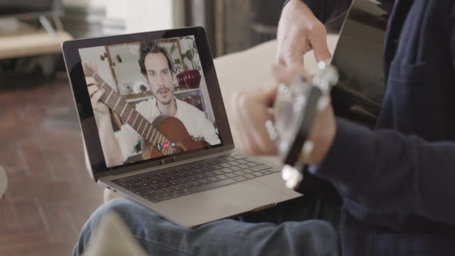 vídeos y material grabado en eventos de stock de online education, man learning guitar lesson during video call with tutor from home - músico