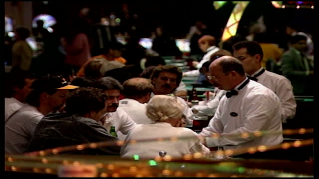 online gambling company executive arrested back view of people seated at card table in casino croupier stands before them close shot of spinning... - card table stock videos and b-roll footage