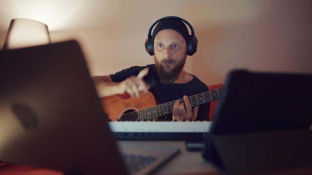 online-gitarrenlehrer im video-chat am laptop lehren gitarre während videokonferenz, home office - musiker stock-videos und b-roll-filmmaterial