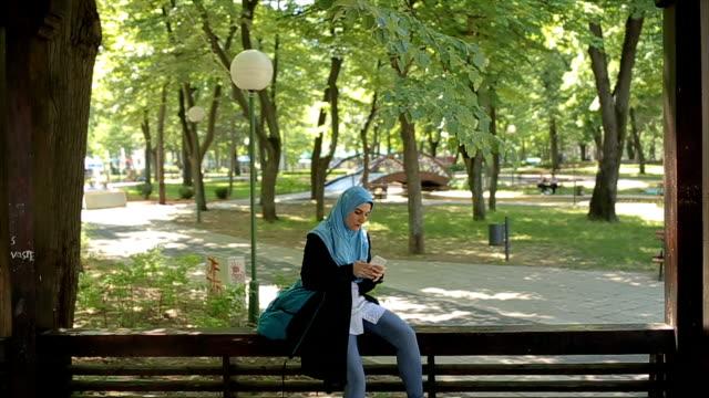 vídeos de stock, filmes e b-roll de on-line de férias, jovem e moderna garota muçulmana, digitando no celular - vestuário modesto