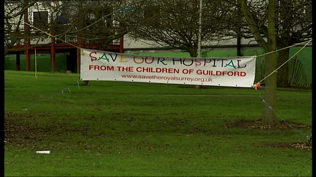 online petition to prevent closure of the royal surrey county hospital grass verge with banner saying 'save our hospital' hanging from trees - petition stock videos & royalty-free footage