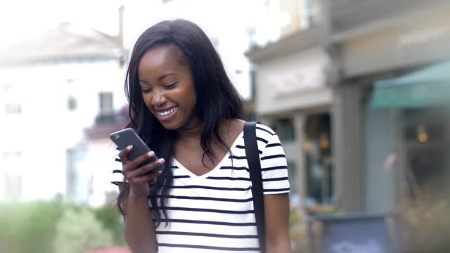 Online phone message outdoors. Young black woman.