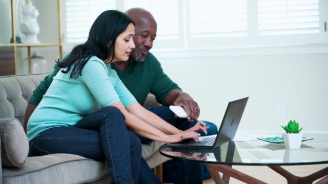 online shopping from home. the mature couple sitting together on a couch and using a pc laptop to finding things on the internet. - 50 54 years stock videos & royalty-free footage