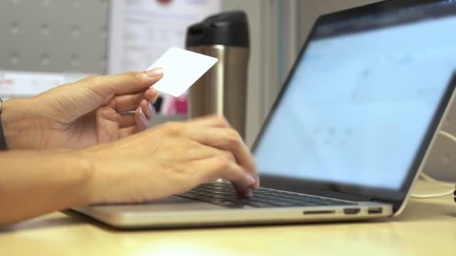 online shopping, kvinna hand innehar kredit kort och skriva på bärbar dator för betalning på hem sida online på internet. - avlägsen bildbanksvideor och videomaterial från bakom kulisserna