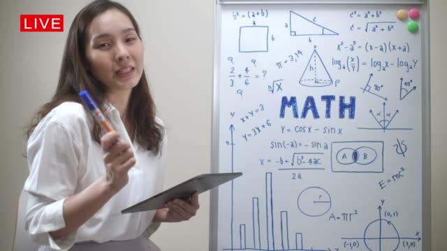 vídeos de stock e filmes b-roll de online teaching, asian female teacher math teaching remotely at her home, working at home - aula de formação