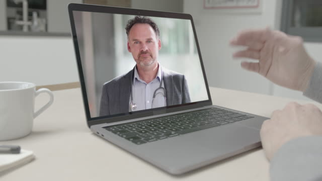 online video call via laptop of male doctor consulting sick man talking in kitchen. medicine, healthcare, technology - remote location stock videos & royalty-free footage