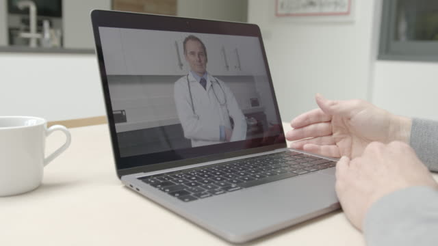 online video call via laptop of male doctor in white lab coat consulting sick man talking at kitchen table. medicine, healthcare, technology - general practitioner stock videos & royalty-free footage