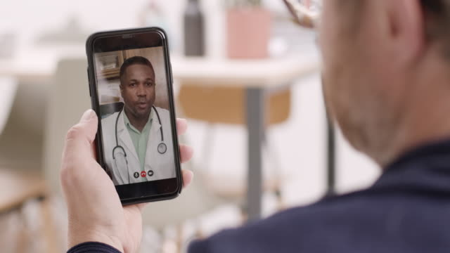 vídeos de stock e filmes b-roll de online video call via smart phone of male doctor consulting sick man at home - doctor
