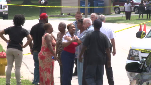 KTVI Onlookers And Police gathered near the crime scene hours after Michael Brown was shot on August 9 2014 in Ferguson Missouri
