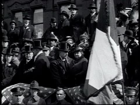 vidéos et rushes de ws onlookers in coats and top hats on the sidelines talking us flags / new york city new york united states - 1910 1919
