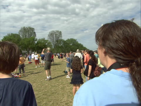 onlookers stand on the mall in washington d.c. to watch the space shuttle discovery, mounted atop a modified airplane, fly over. - space shuttle discovery stock videos & royalty-free footage