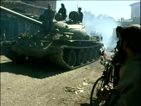 vidéos et rushes de onlookers watch as northern alliance tank drives through streets of small afghan town war in afghanistan 2001 - guerre d'afghanistan : de 2001 à nos jours