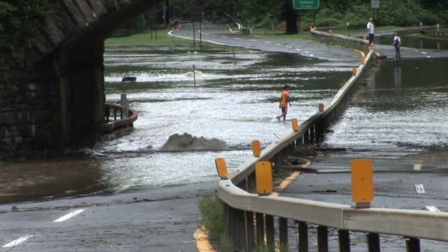 onlookers watching river overflow on bronx river parkway after flooding was caused by hurricane irene / water bubbling up from ground / children... - hurricane irene stock videos & royalty-free footage