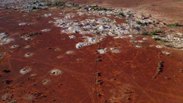 opal mining town with red desert landscape and white mine tailings, outback australia, aerial view - weather stock videos & royalty-free footage