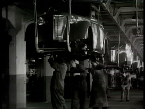 vídeos de stock e filmes b-roll de opel car factory vs car assembly line cars hanging german worker placing tire installing rear seat line of opel cars driving out of factory - general motors