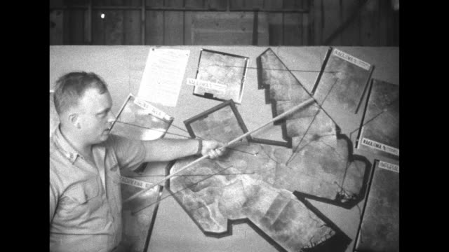 Open air structure with men seated in rows and along wall at rear / US officer using pointer to note areas on map during World War II planning...