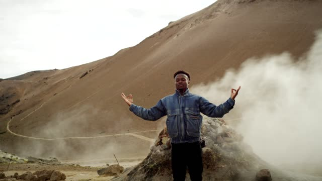 open arms. african ethnicity man enjoying hissing steam vents - geyser stock videos and b-roll footage