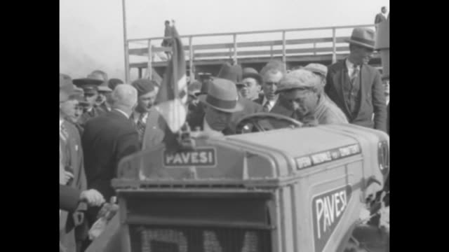 open car carrying benito mussolini pulling into worksite, crowd of men awaiting him, tractor in foreground / mussolini walking with group of... - benito mussolini stock videos & royalty-free footage