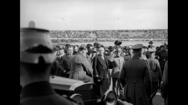Open car carrying German president Paul von Hindenburg enters stadium / crowd on field being held back / Hindenburg in military uniform gets out of...