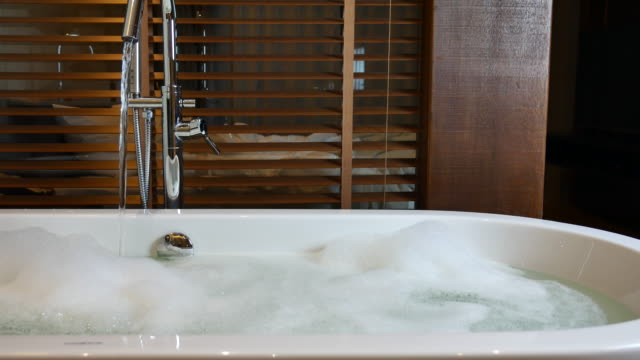open faucet bathtub in bathroom - vasca da bagno video stock e b–roll