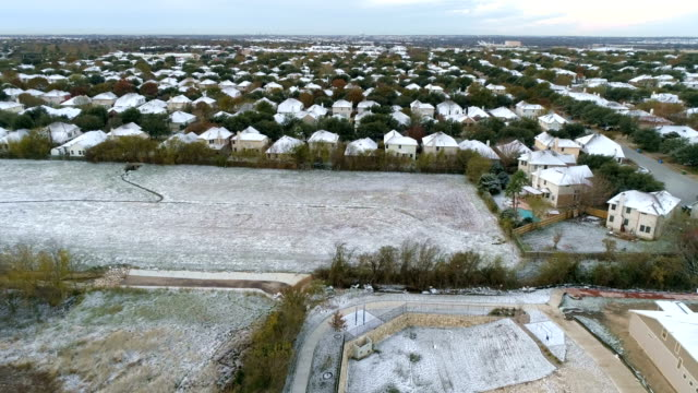 open field with snow and suburb in north austin rare weather snow event in central texas - texas stock videos & royalty-free footage