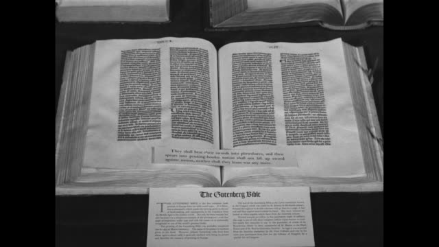 vidéos et rushes de open gutenberg bible and two other open bibles lying on table / cu open gutenberg bible with written pages in latin script and piece of paper... - religion