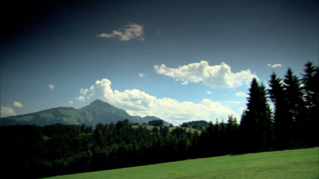 vidéos et rushes de open meadow lined w/ evergreen trees to chalet home, austrian alps mountains bg. - chalet