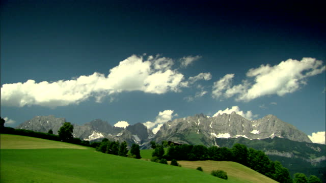 vidéos et rushes de open meadows lined w/ trees, austrian alps mountains bg. no people. - chalet
