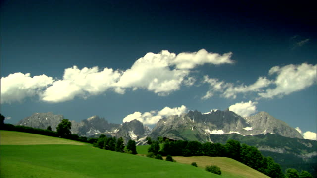 XWS Open meadows lined w/ trees Austrian Alps mountains BG No people